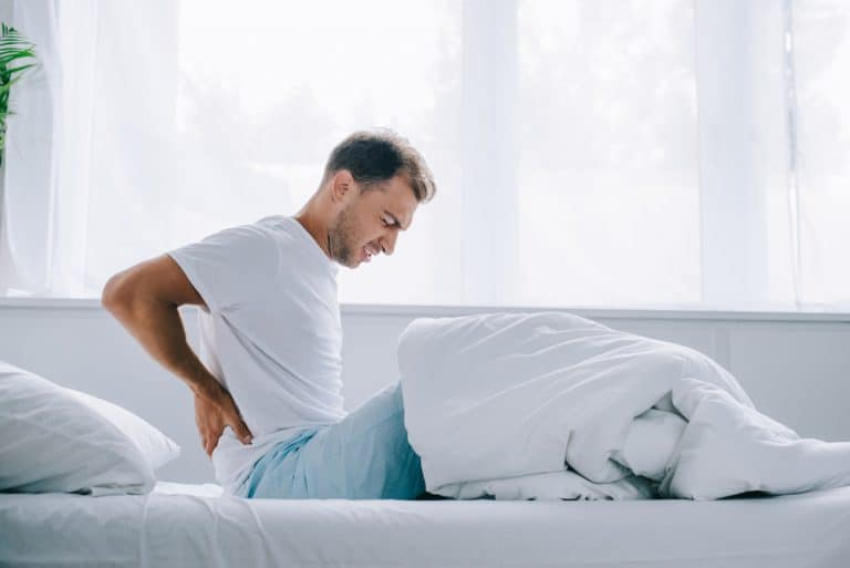a man sitting up in bed holding his back in pain