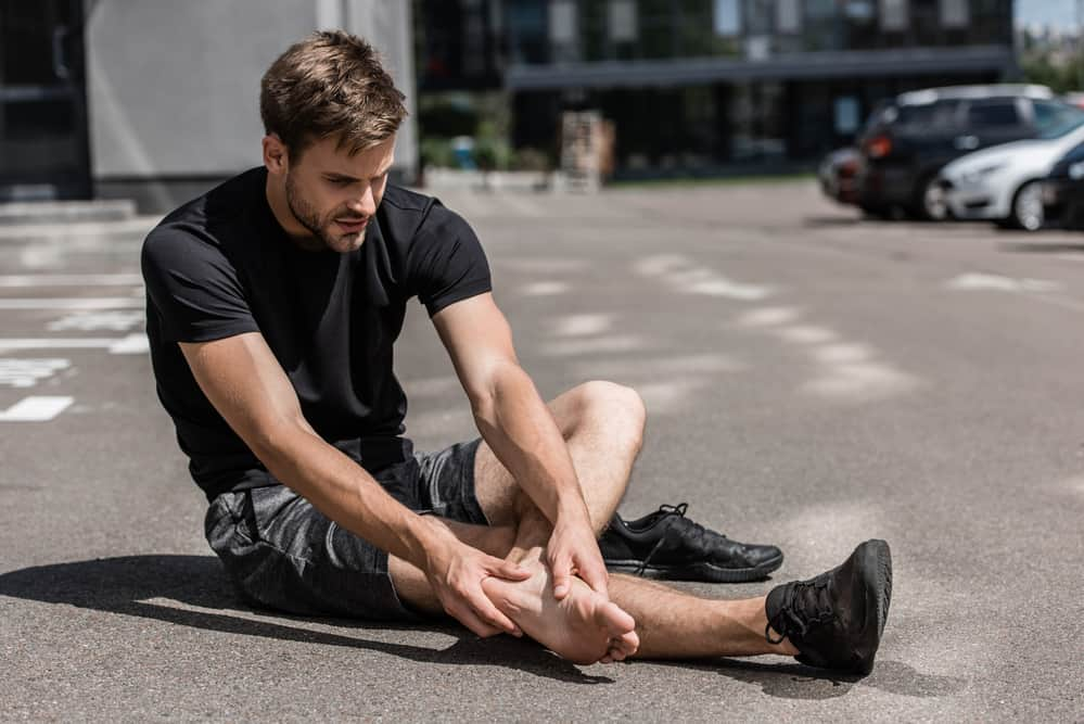 man holding his foot in pain, a decorative image for an article about fascia scraping for plantar fasciitis