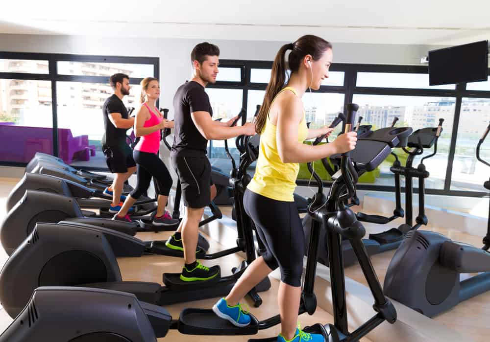 people at a gym using elliptical machines
