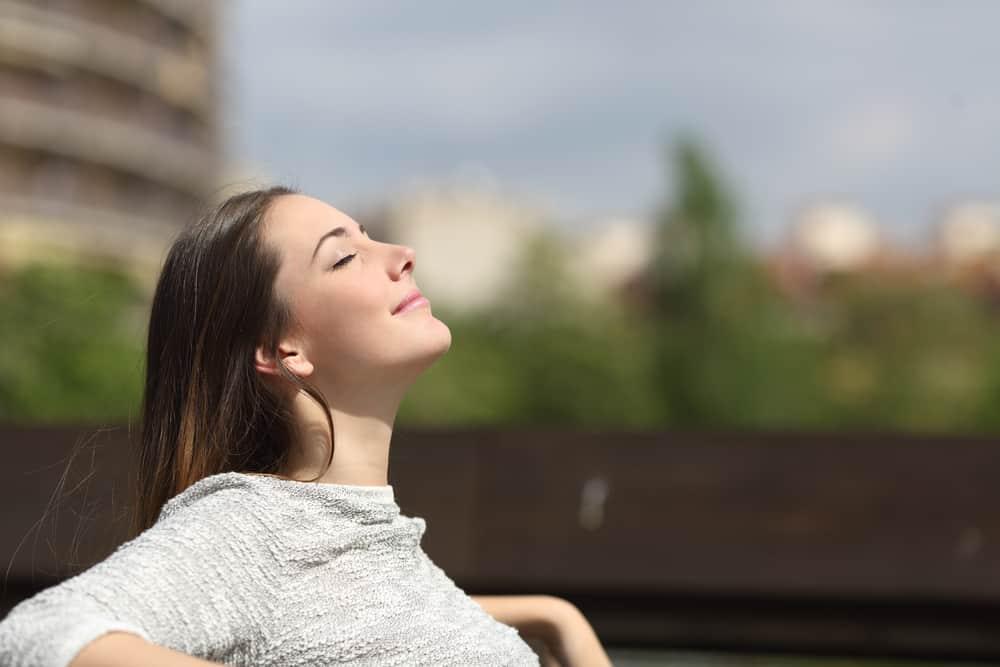 woman sitting outside breathing deeply
