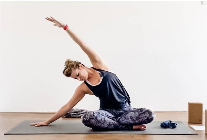 woman doing yoga seated side bend