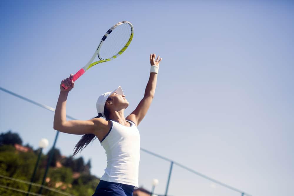 woman playing tennis serving a ball